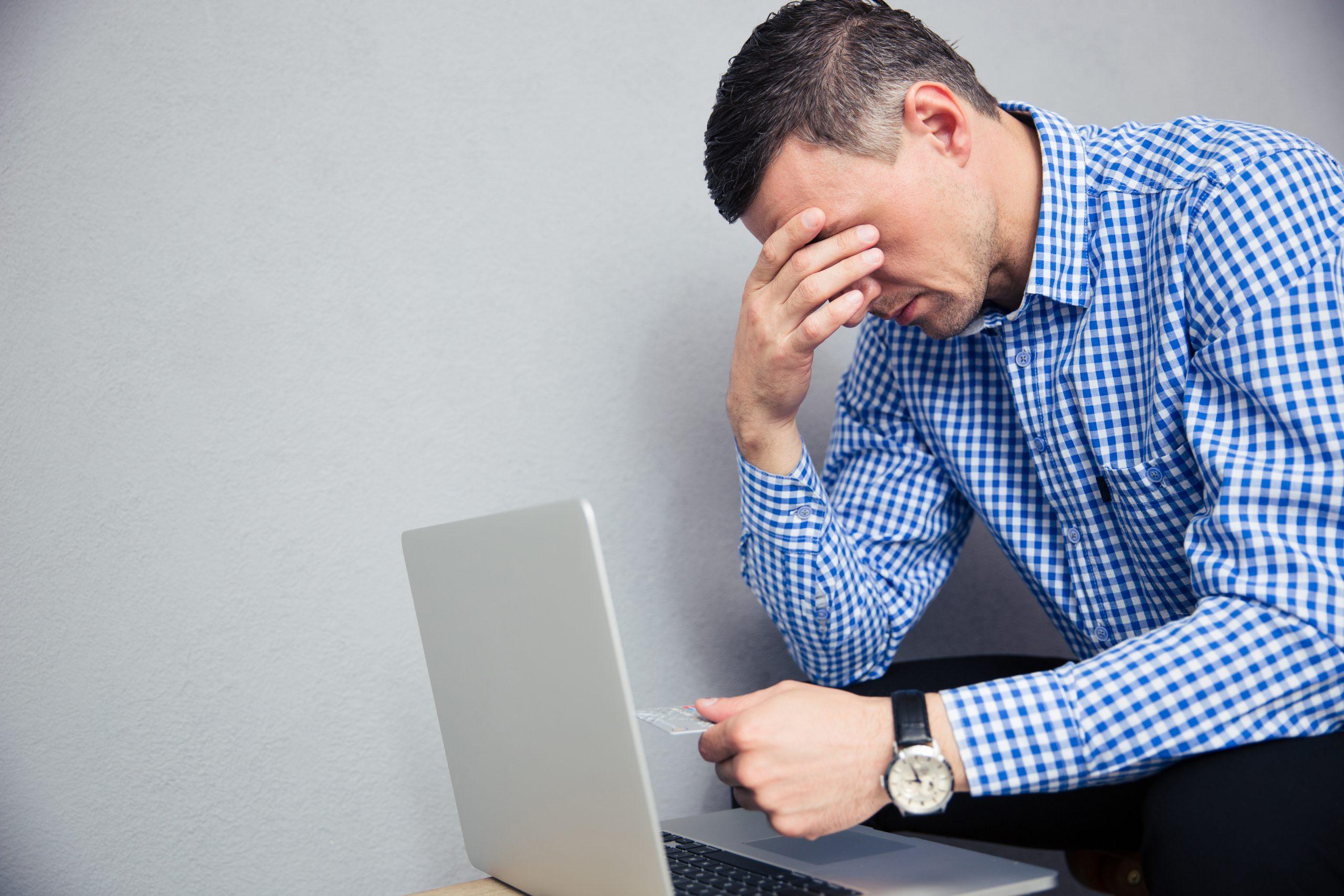 depressed man holding credit card scaled