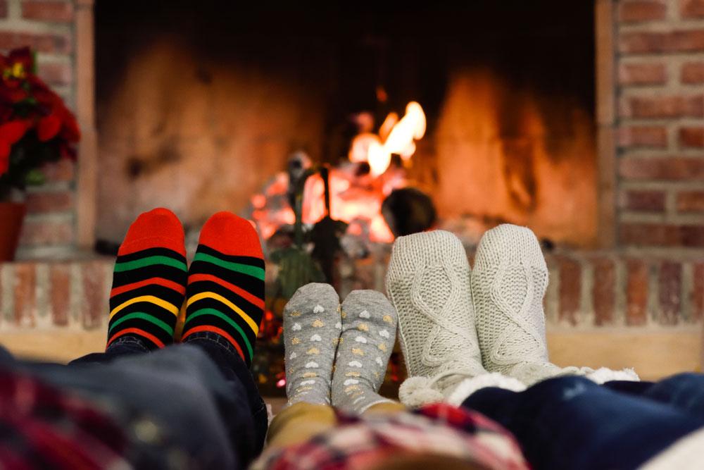 feet christmas socks near fireplace relaxing home