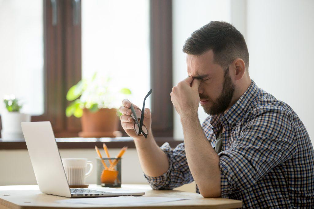 stressed male massaging nose bridge suffering from headache 1