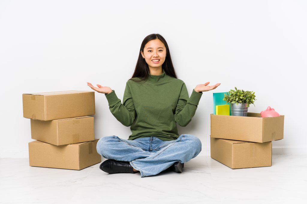 young chinese woman moving new home makes scale with arms feels happy confident