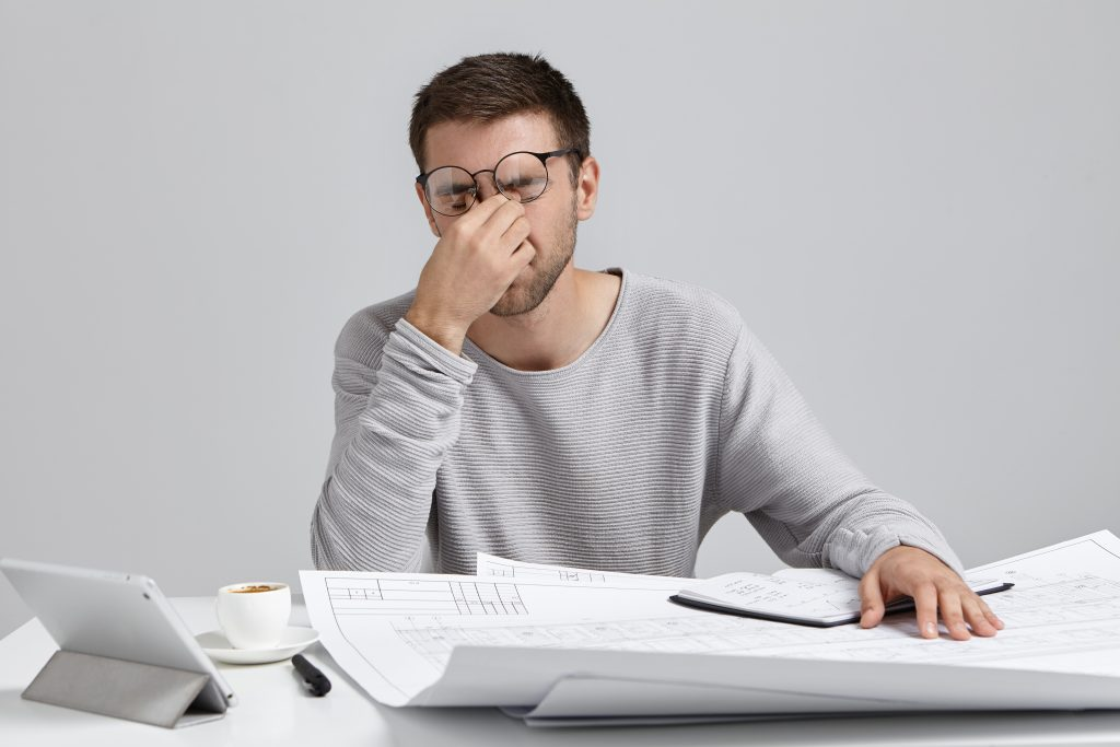 stess overwork deadline tired unshaven young architect freelancer massaging nose bridge